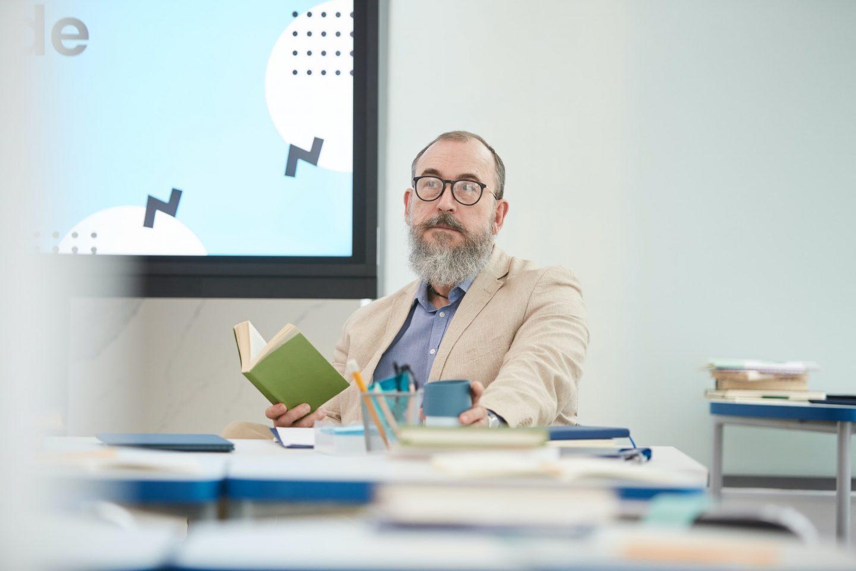 Senior Bearded Professor Sitting at Desk in Class