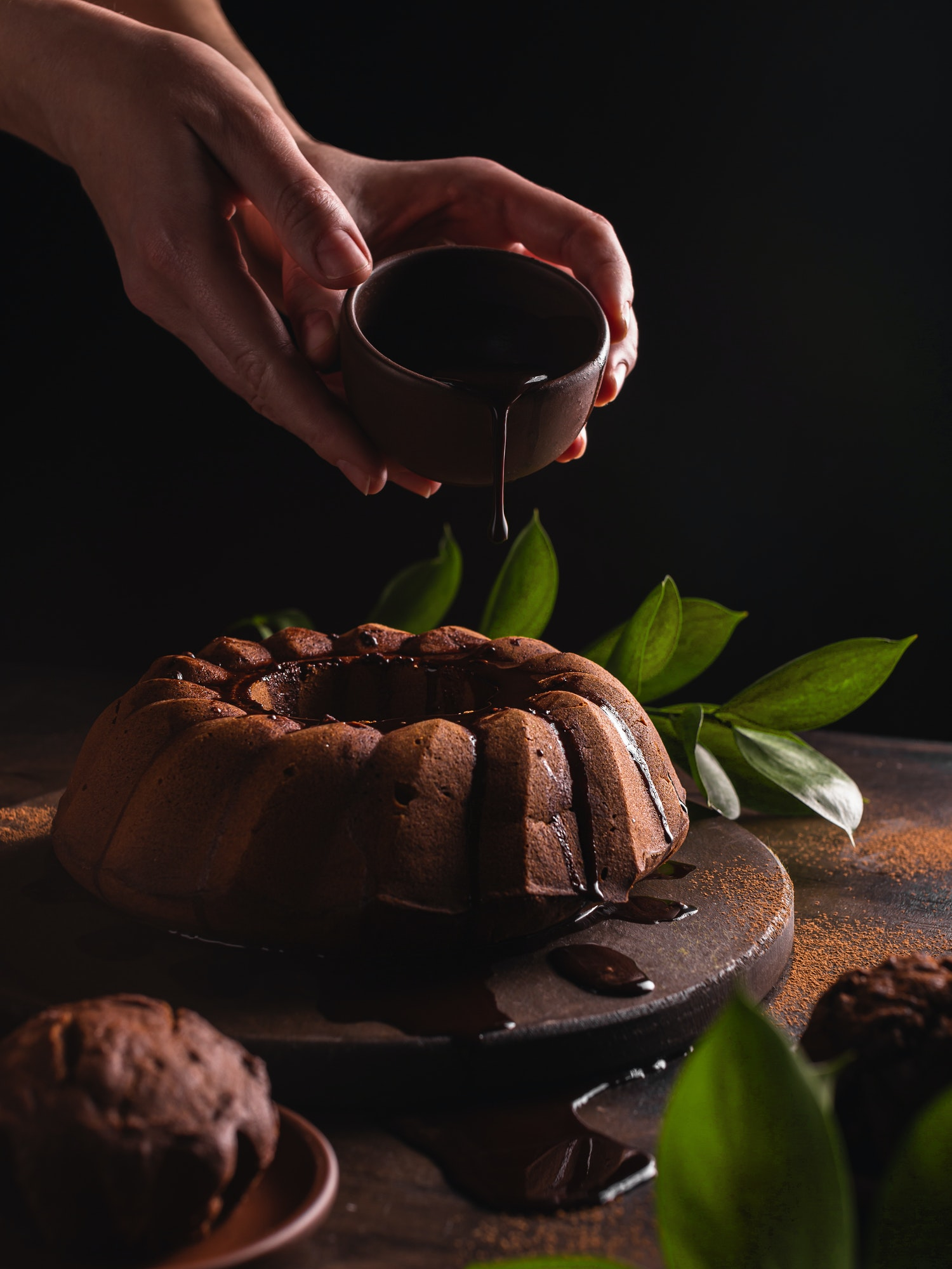 Woman pouring chocolate on a chocolate cake