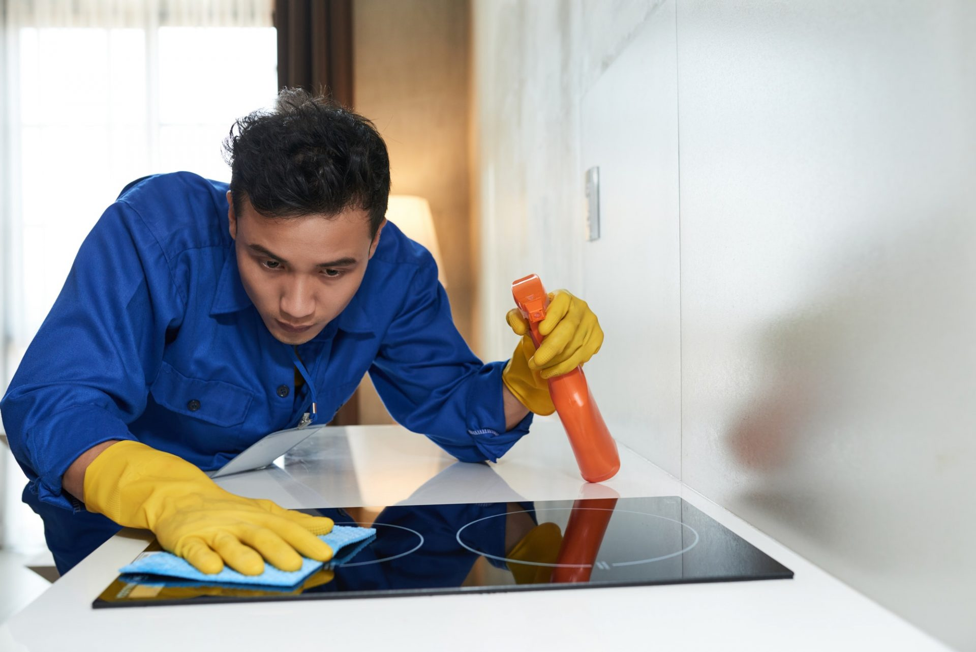 Worker cleaning stove surface