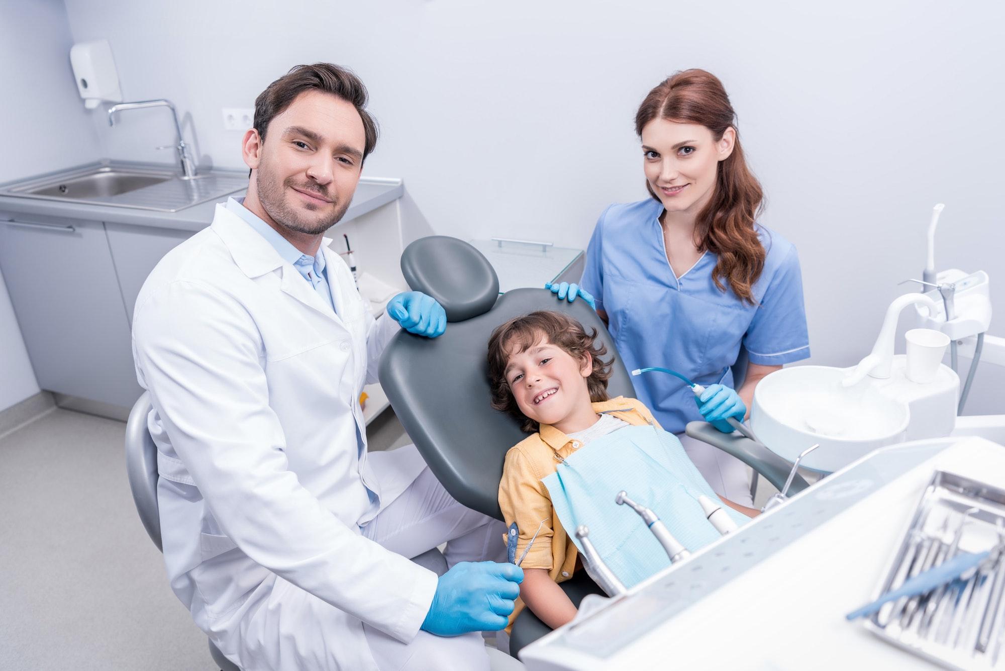 dentists preparing little boy for examining teeth at dentist office