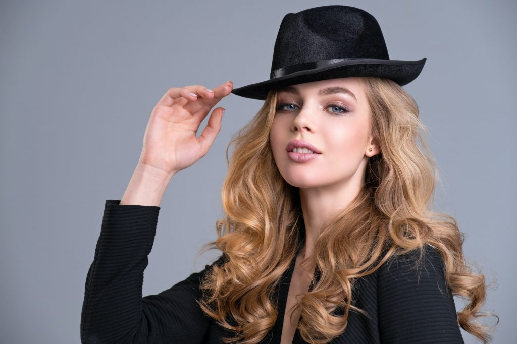 Fashion model in black jacket and black hat.