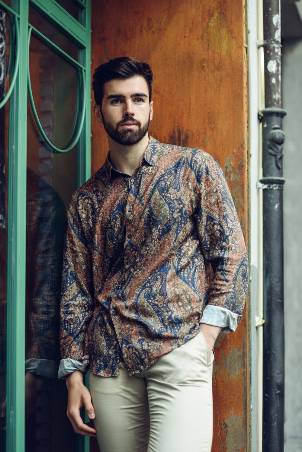Young bearded man, model of fashion, wearing shirt in urban back