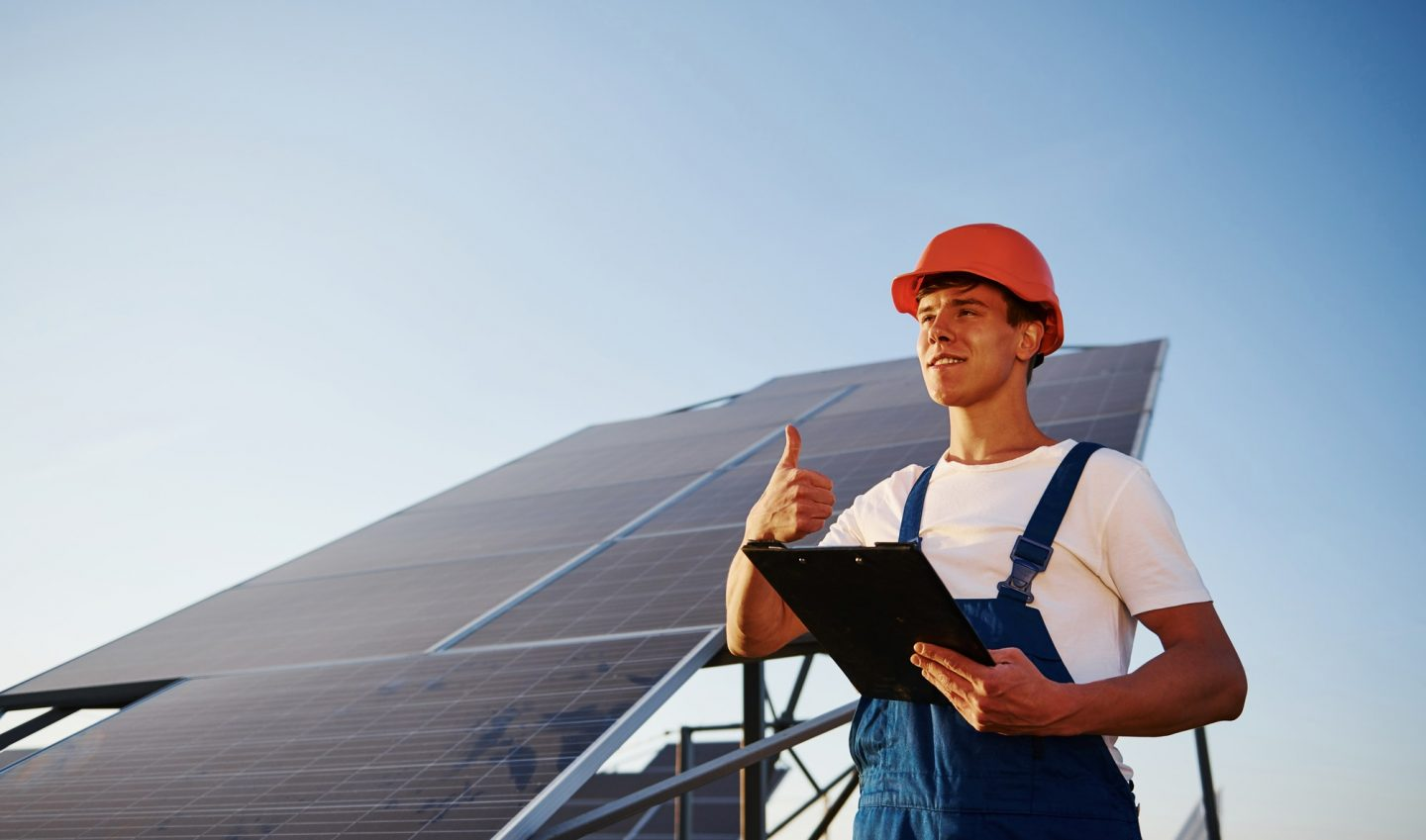 Shows thumb up. Male worker in blue uniform outdoors with solar batteries at sunny day
