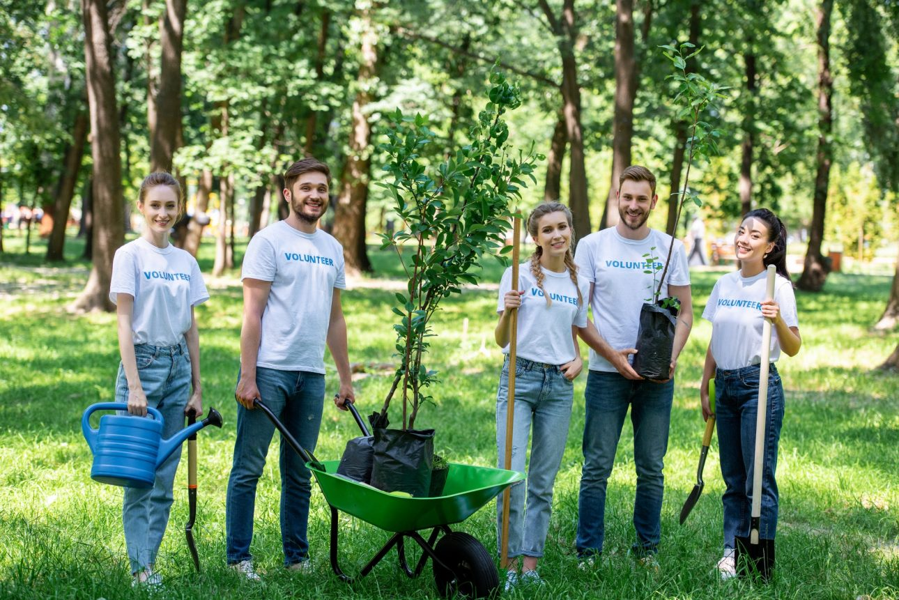 friends volunteering and planting trees in park together