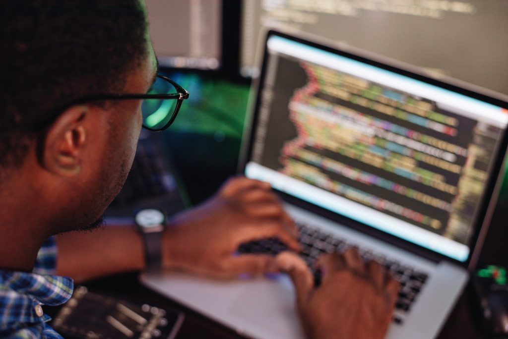 Black male in front of computer screen coding mobile app, web development, computer programming