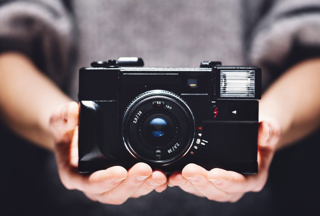 Retro camera in woman's hands. Photography
