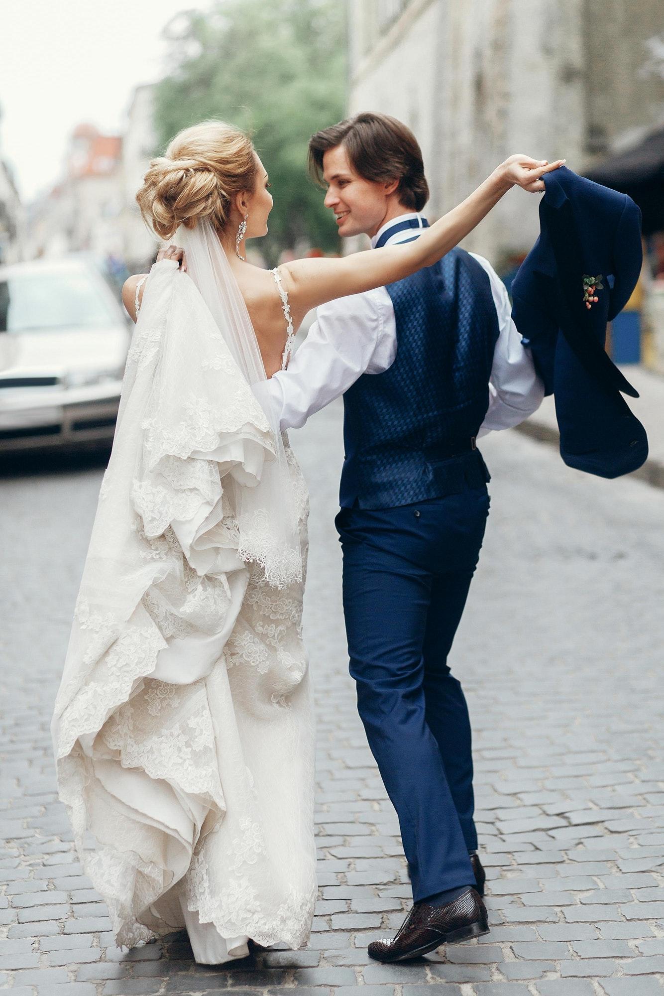 Bride and groom dancing and having fun in city street.