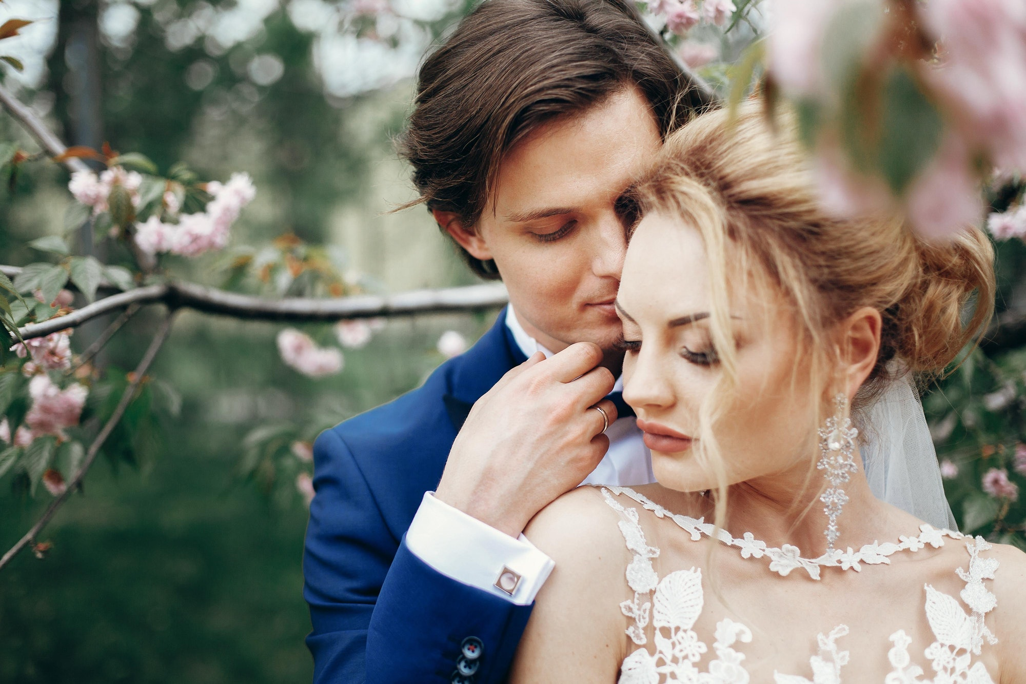 Bride and groom embracing and kissing in park among magnolia flowers