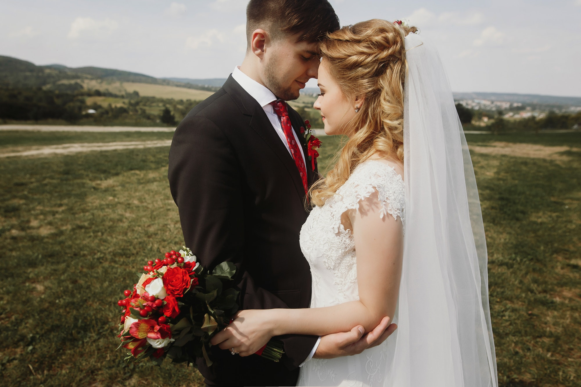 gorgeous bride and groom posing at field