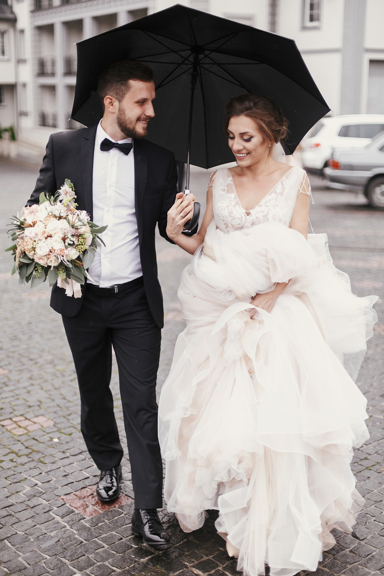 Gorgeous bride and stylish groom walking under umbrella in rainy street and smiling