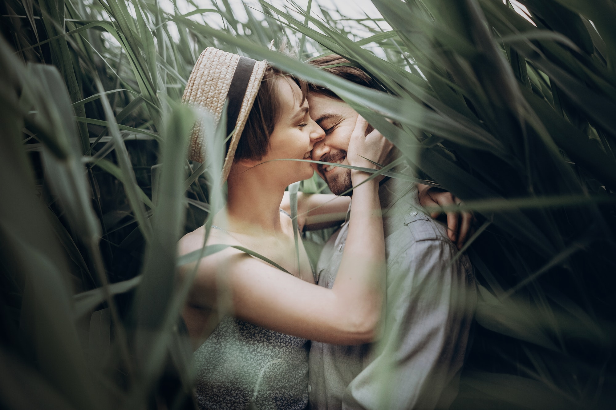 Happy hipster couple embracing at lake in cane