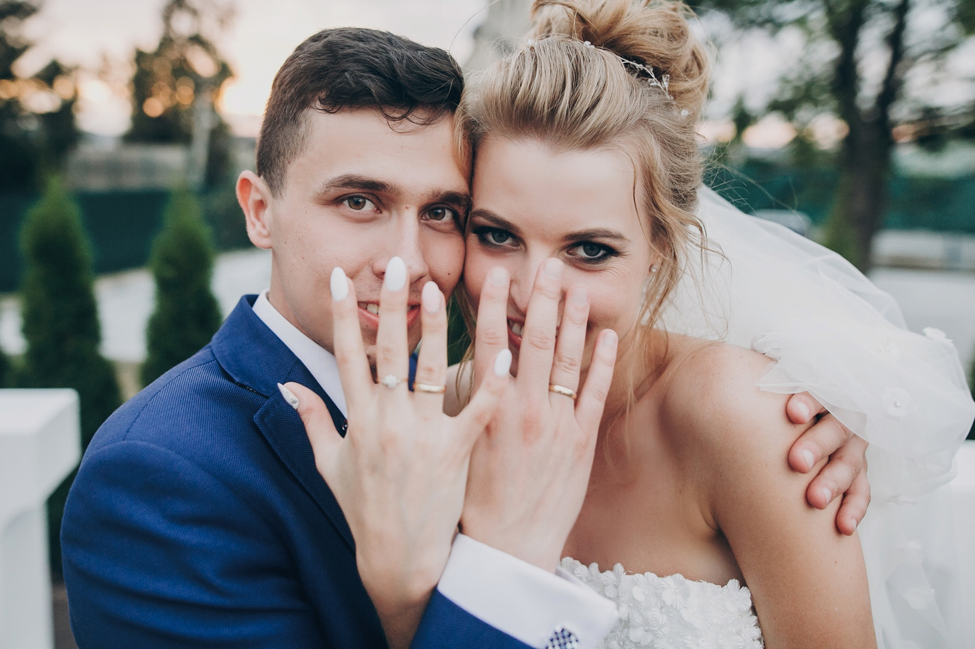 Just married. Stylish happy bride and groom showing hands with wedding rings