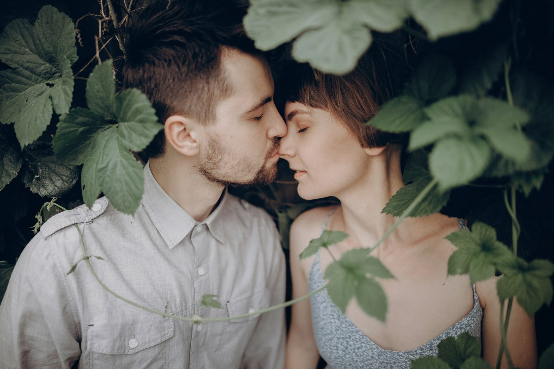 Stylish hipster couple kissing in green leaves, holding hands