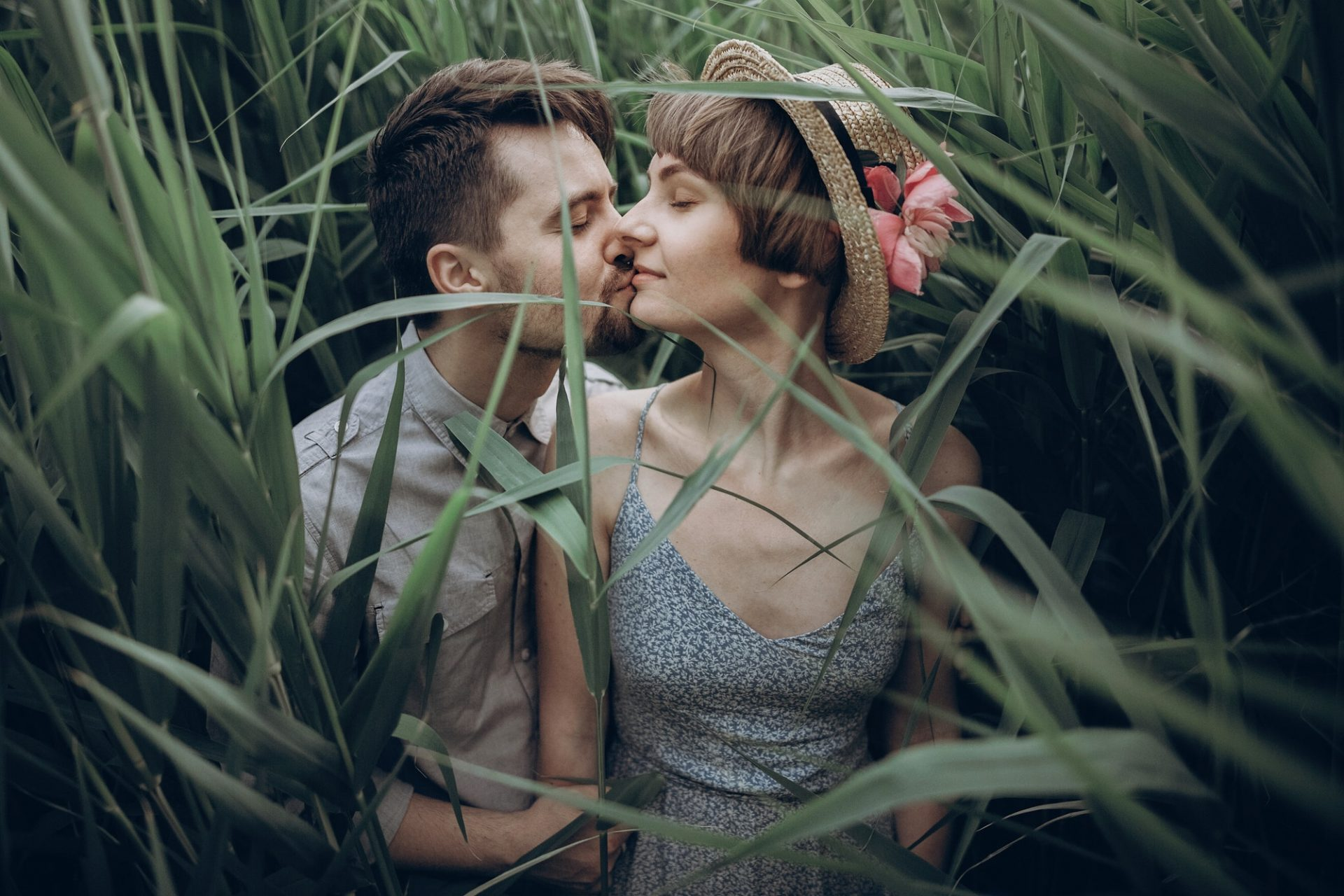 Stylish rustic bride and groom embracing in windy high reed