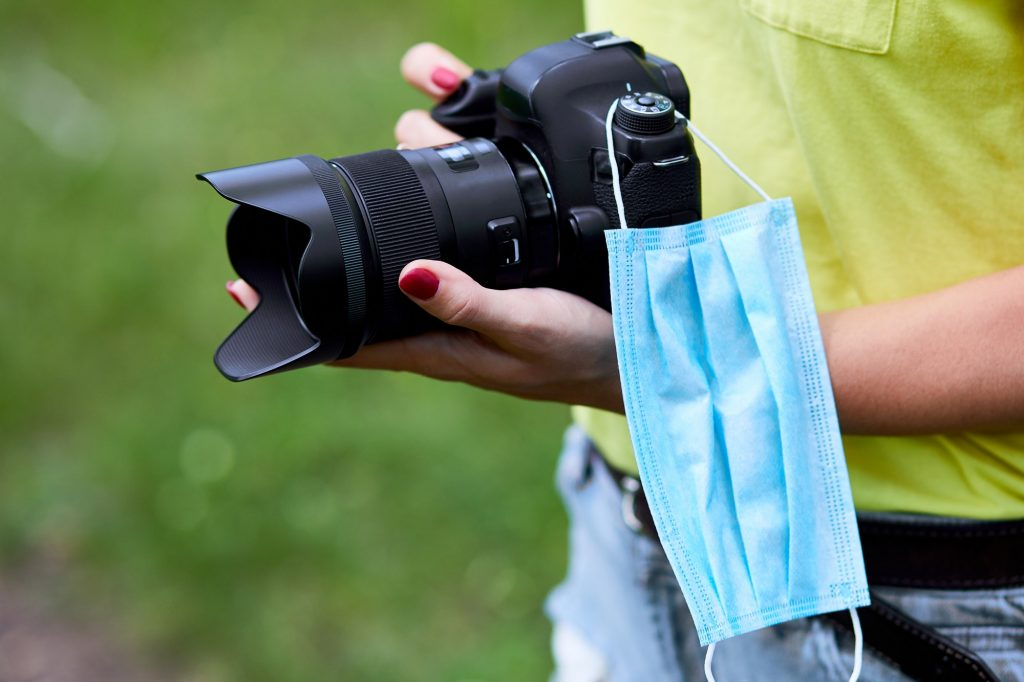 Woman photographer with a photo camera in hand outdoor with protection mask