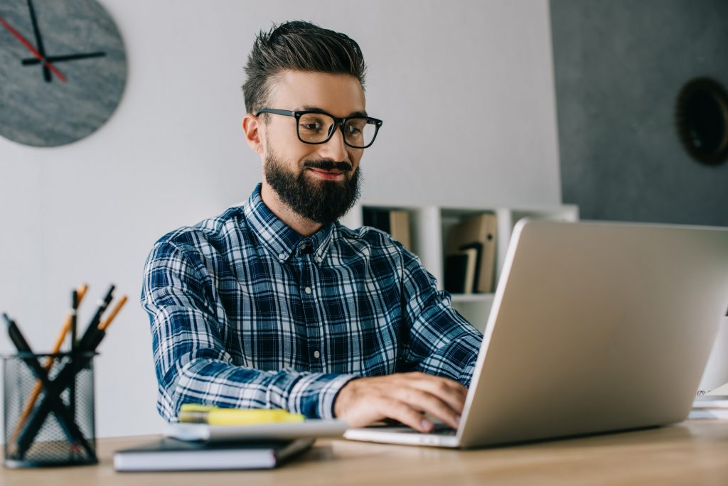 smiling young bearded developer working with laptop