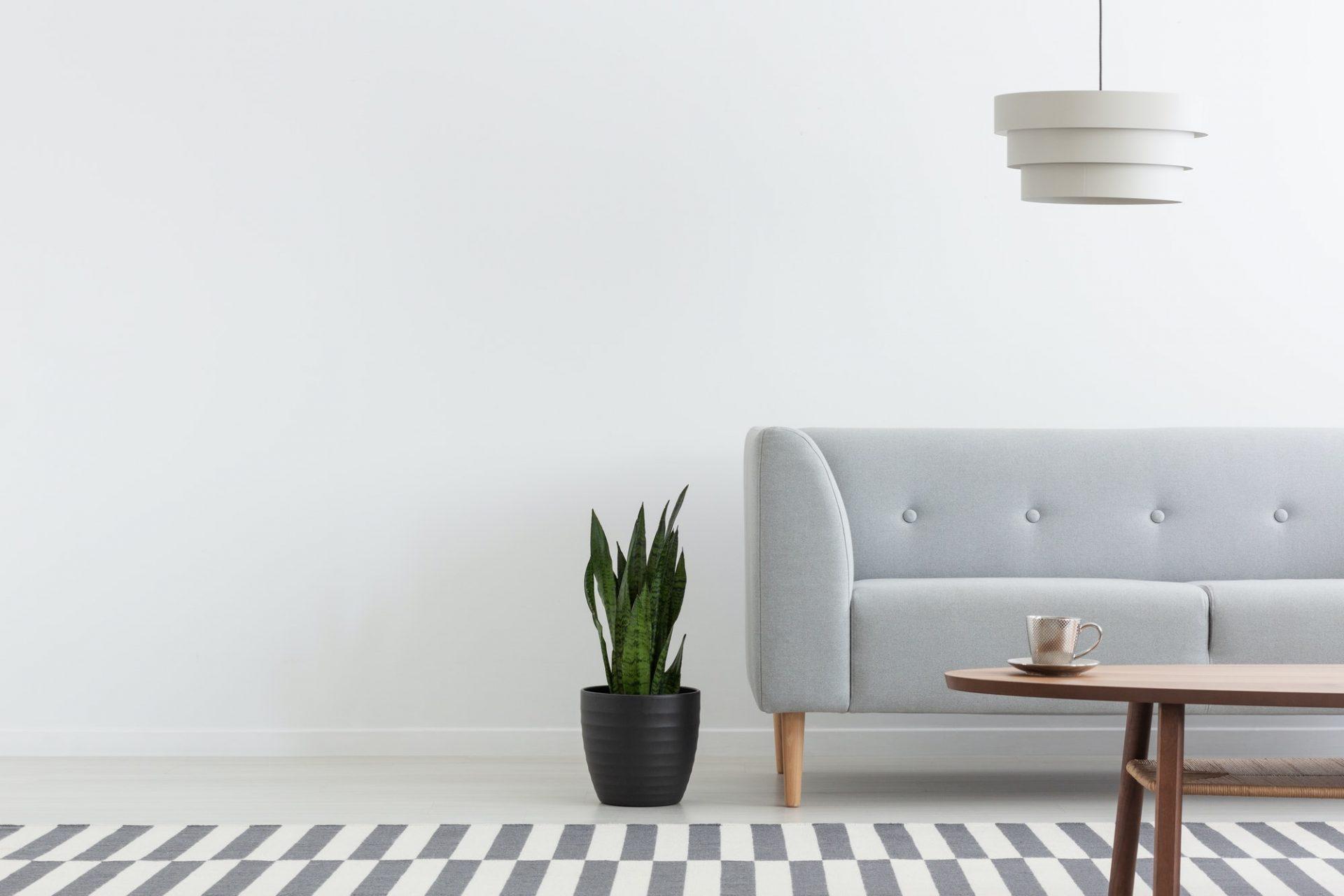Stylish lamp above grey modern sofa in white living room interio