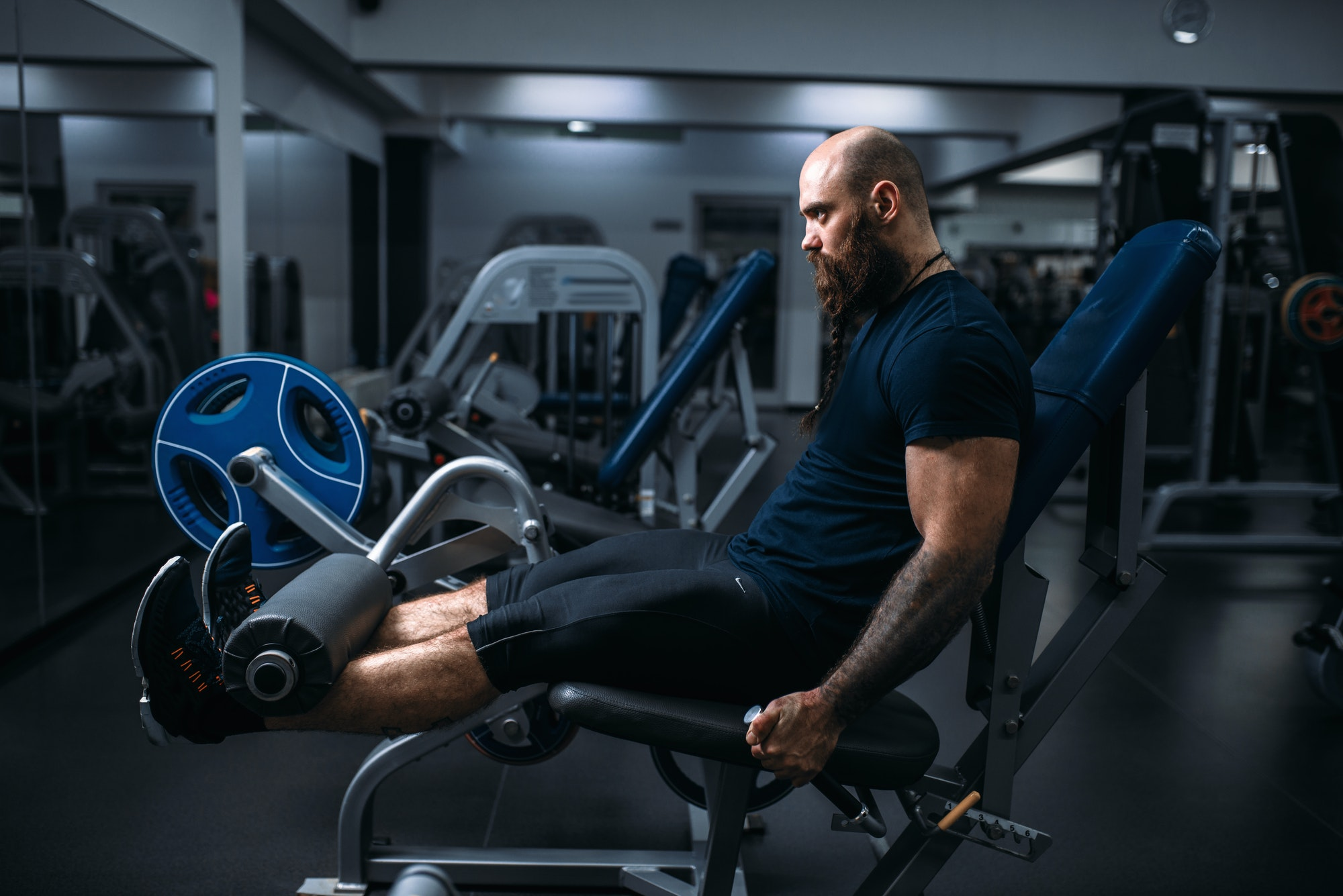 Muscular athlete trains legs on exercise machine