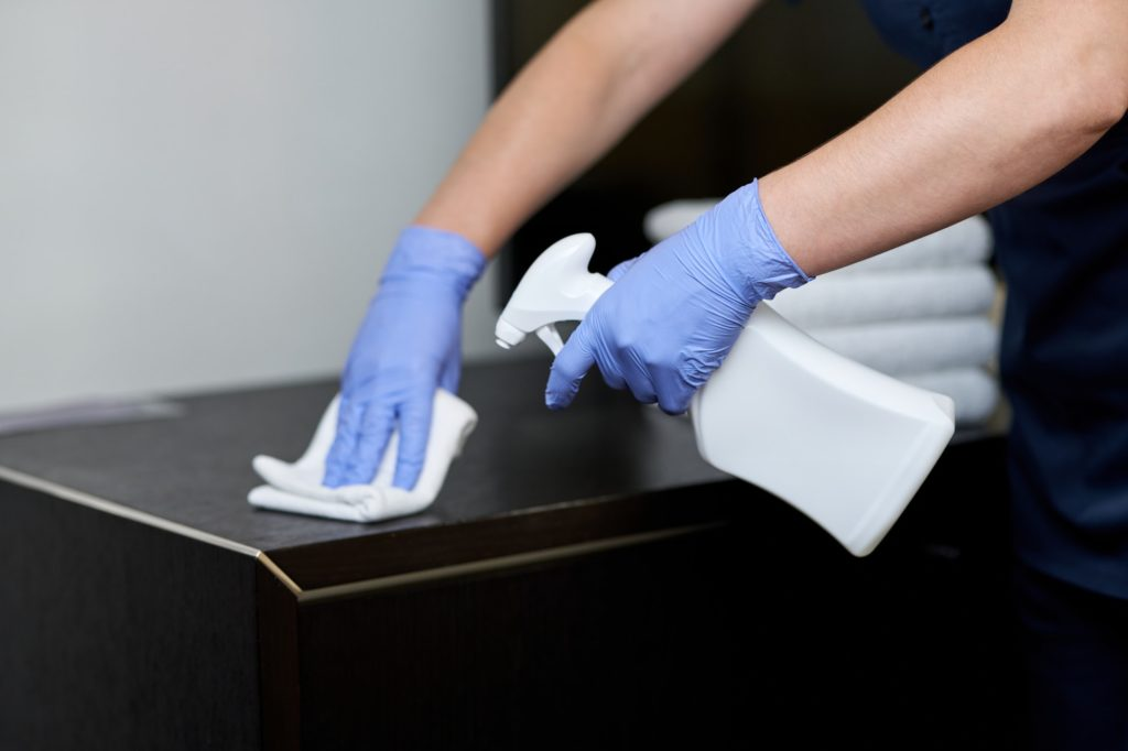 Maid doing disinfection of surfaces in the room