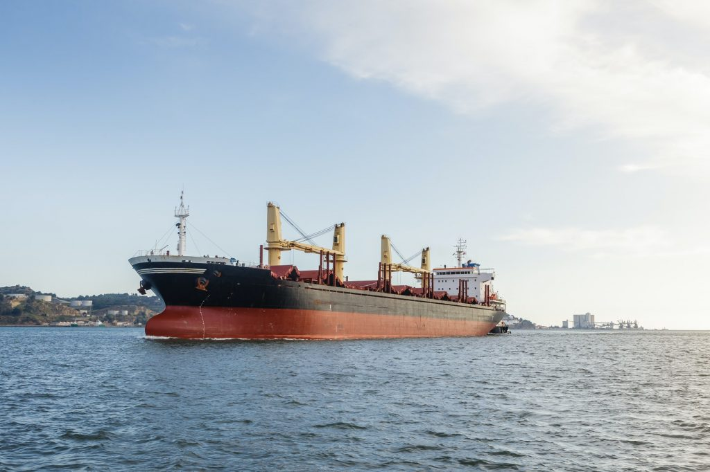 Cargo ships in river being tugged
