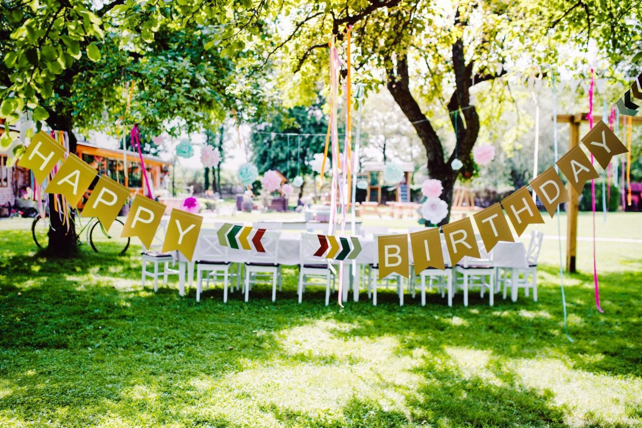 A table set for kids birthday party outdoors in garden in summer.