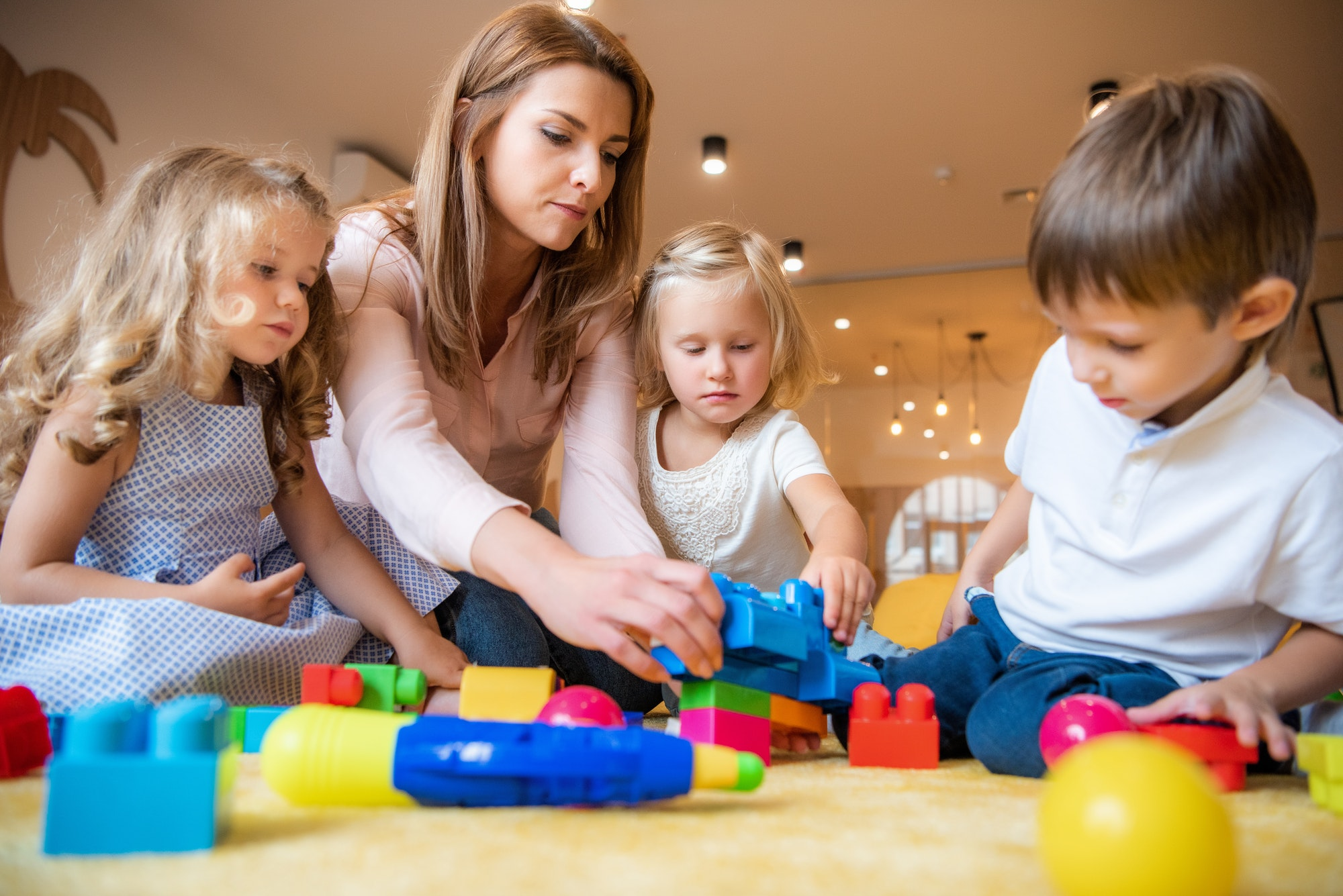 educator and adorable kids playing with constructor in kindergarten