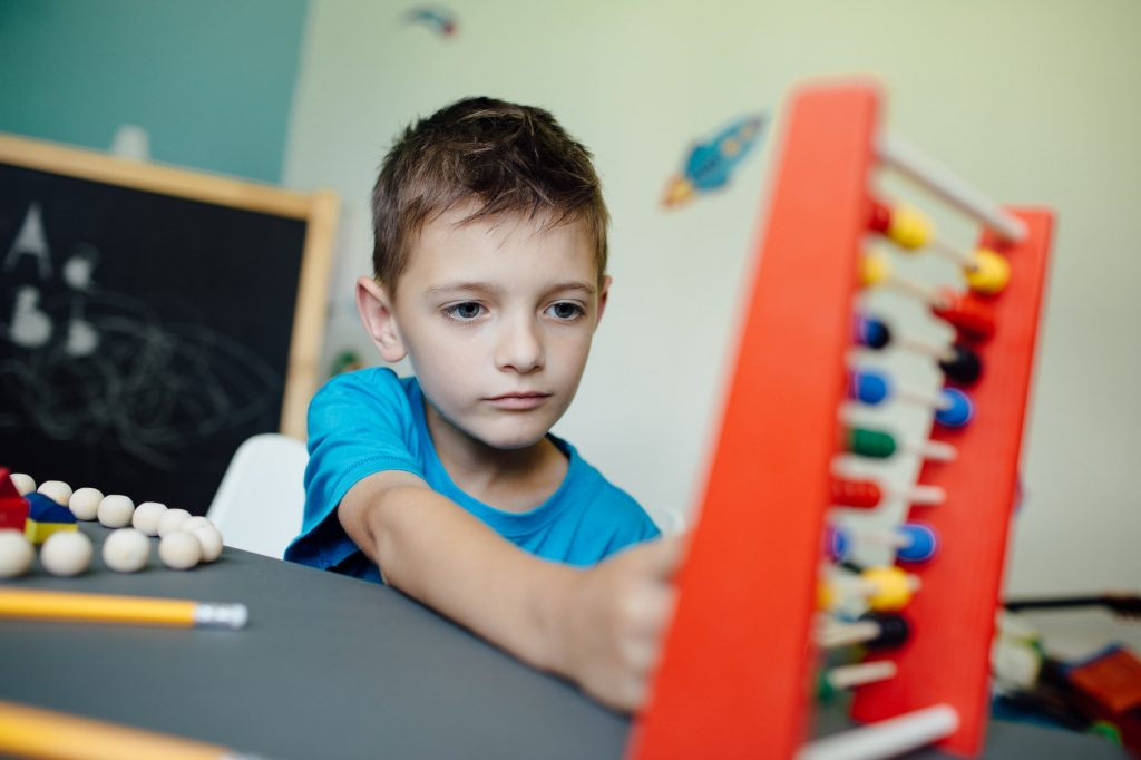 Schoolboy learning maths with an abacus