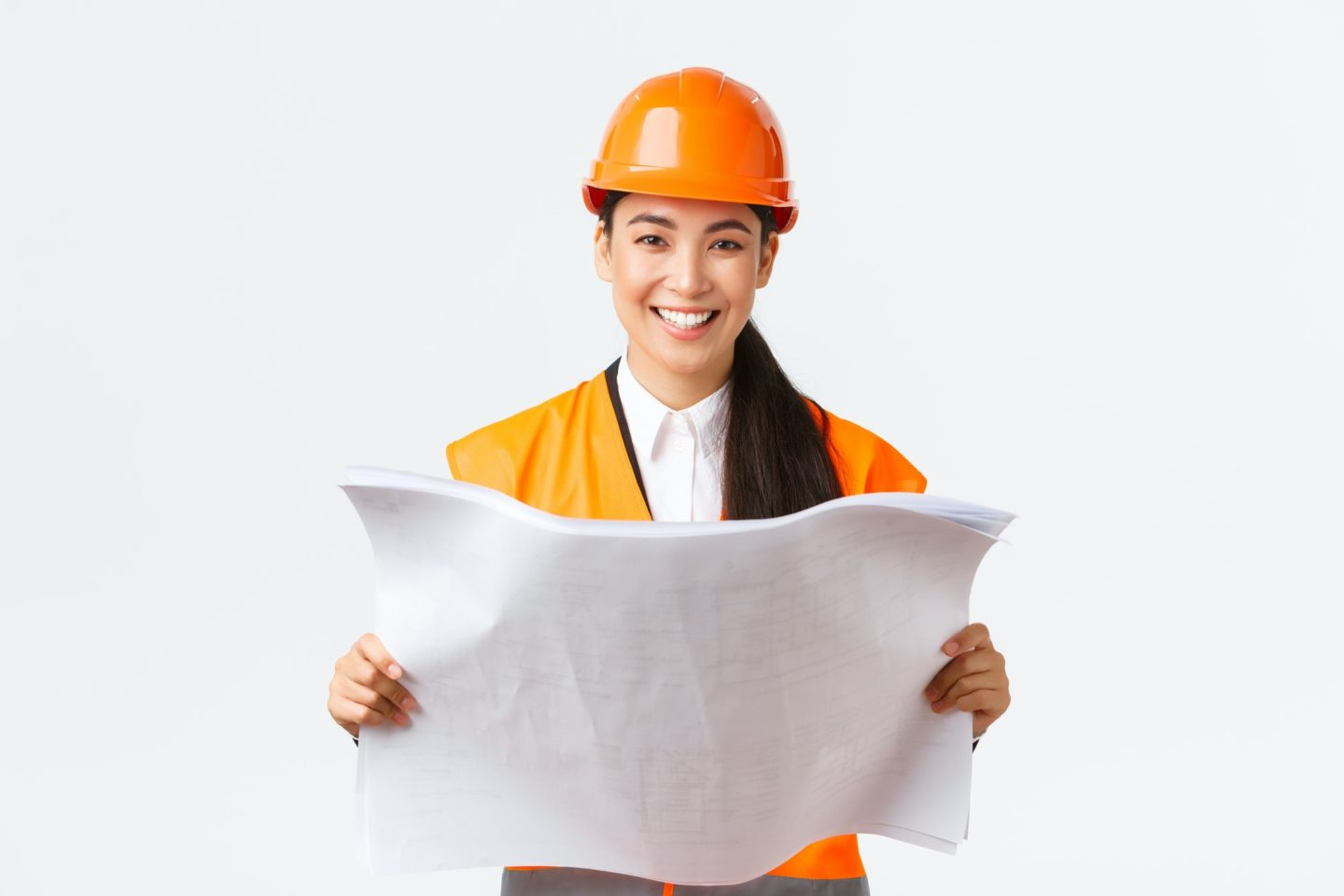 Smiling pretty asian female architect, industrial woman in safety helmet and reflective jacket