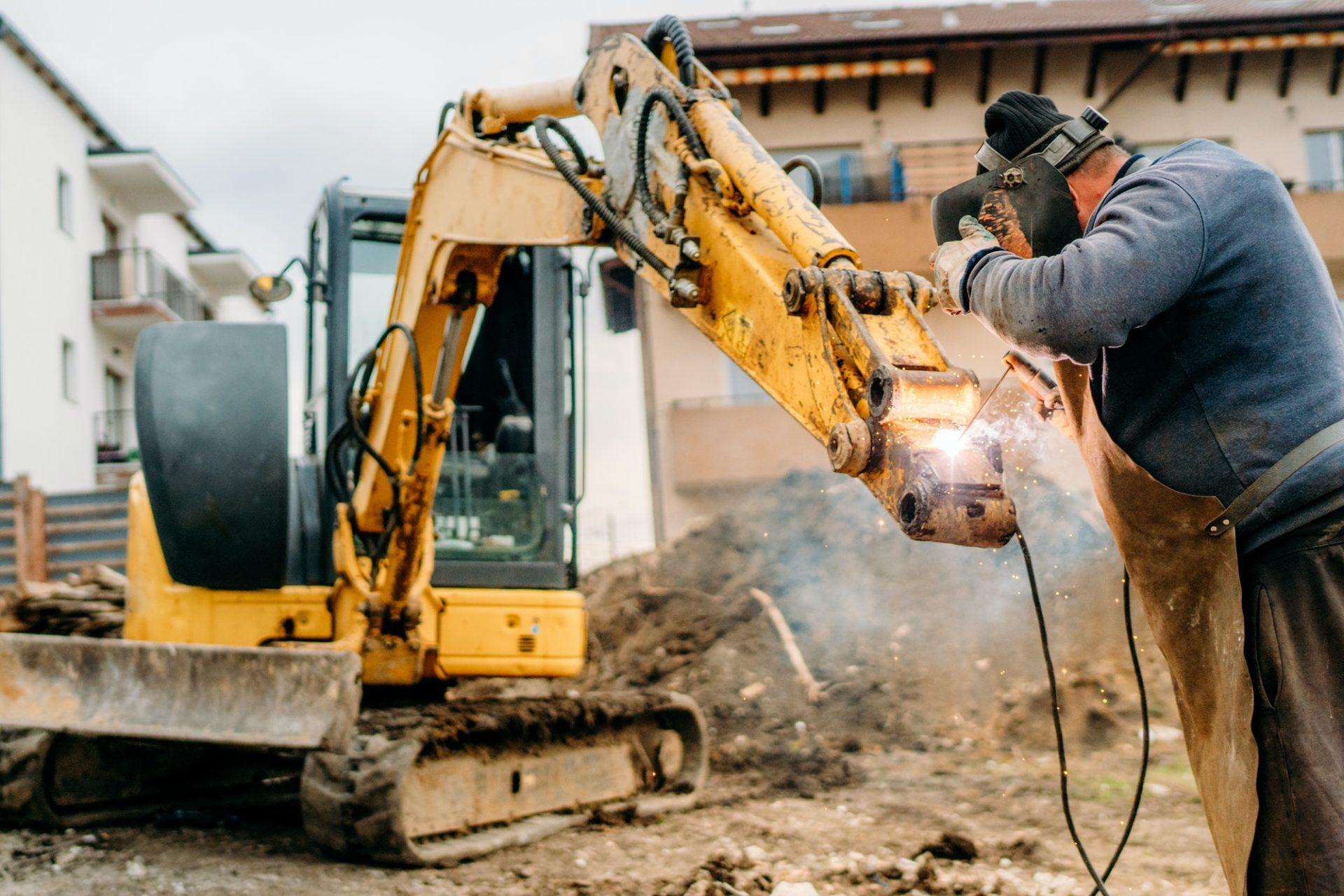 construction and building site, broken excavator and professional welder