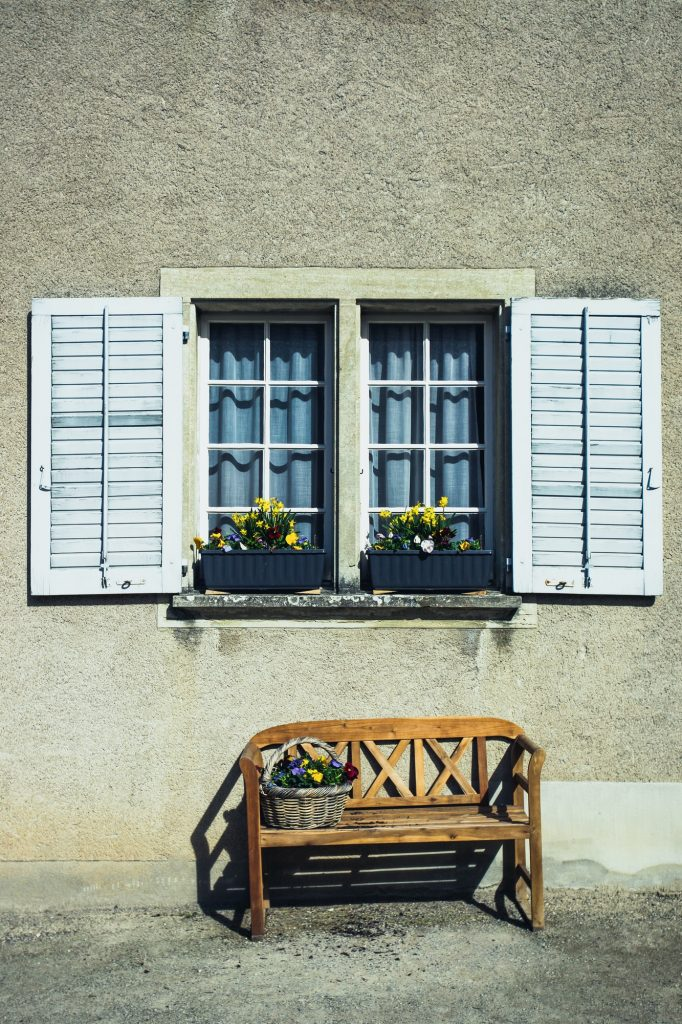 Window with wooden shutters and a bench with flowers