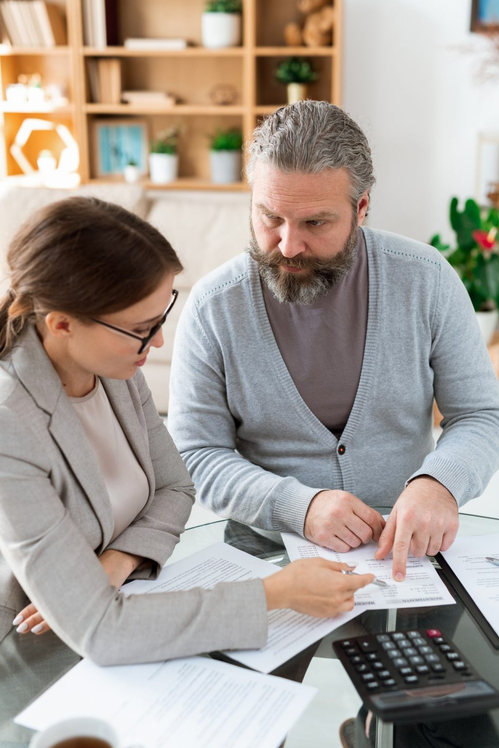 Bearded pensioner consulting with his insurance agent about points of document