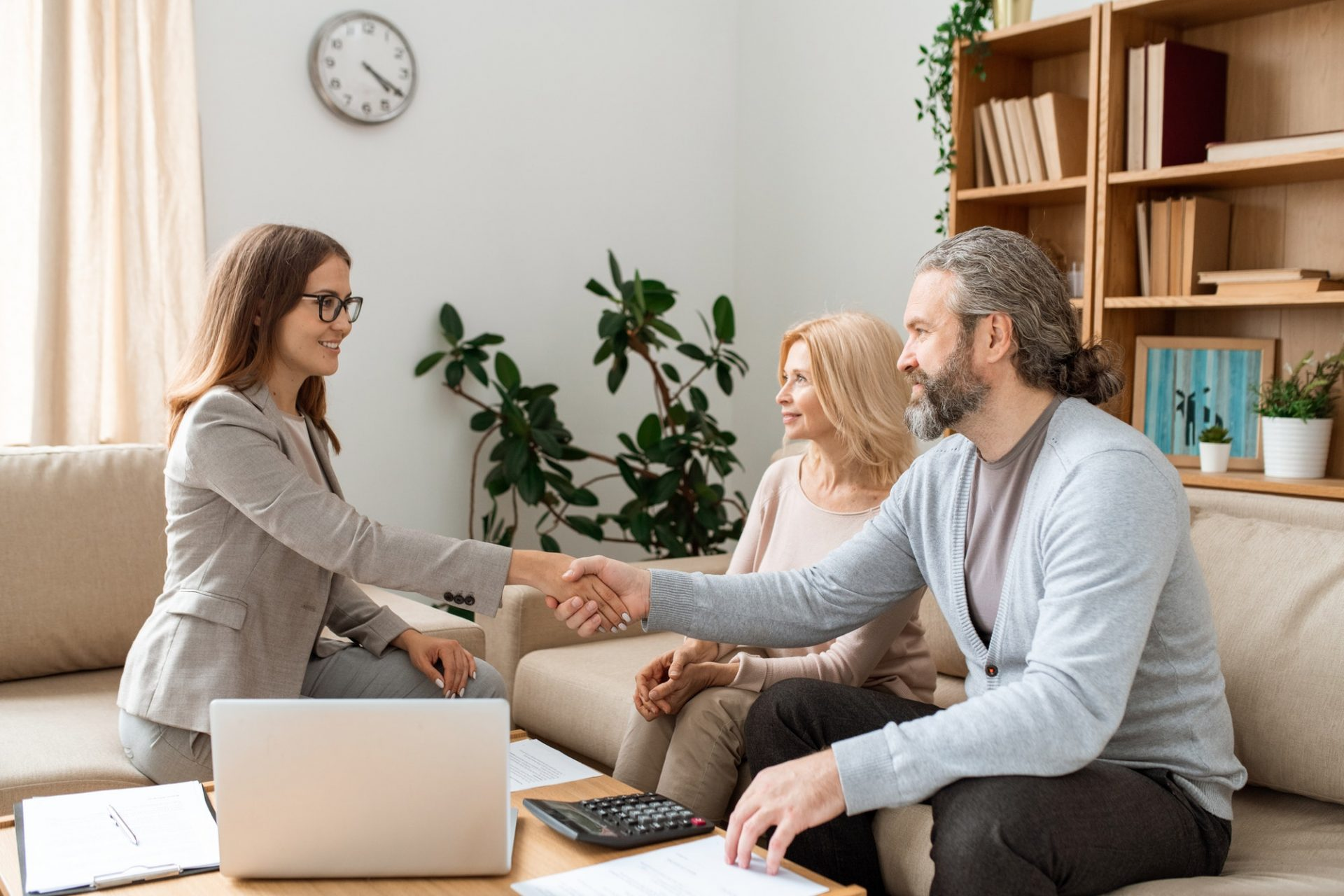 Casual bearded man shaking hand of young female real estate agent over desk
