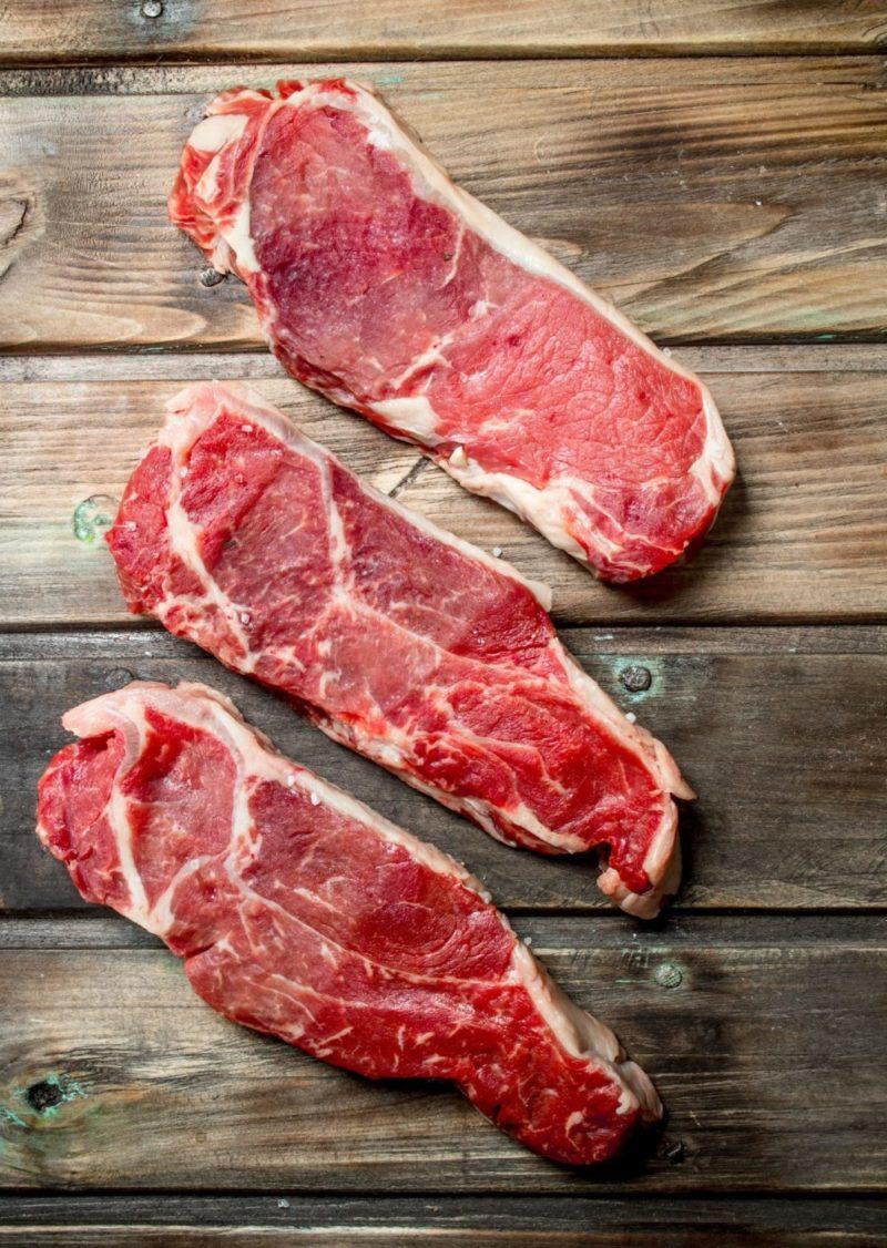 Raw beef steaks .