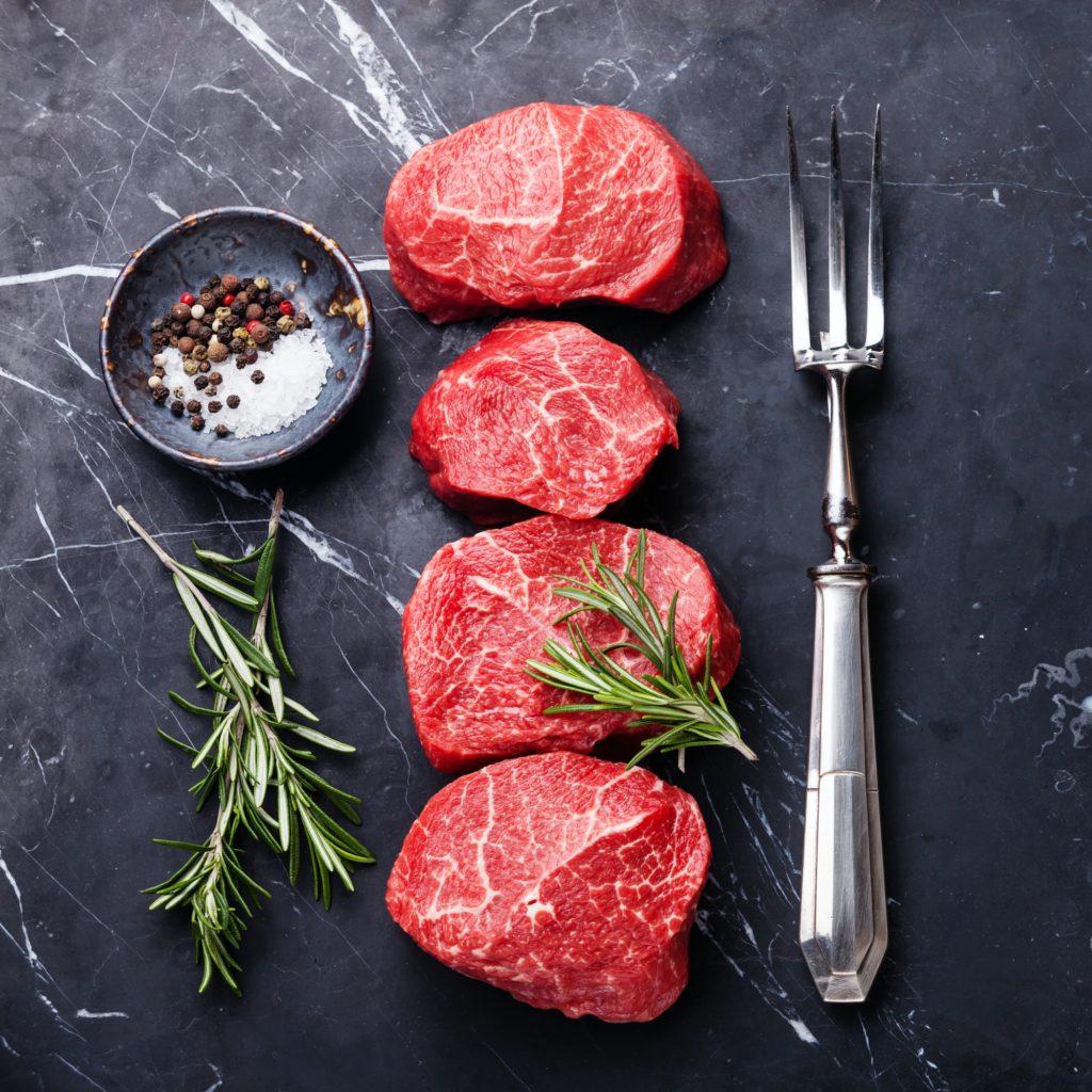 Raw fresh marbled meat Steak, seasonings and meat fork on dark marble background