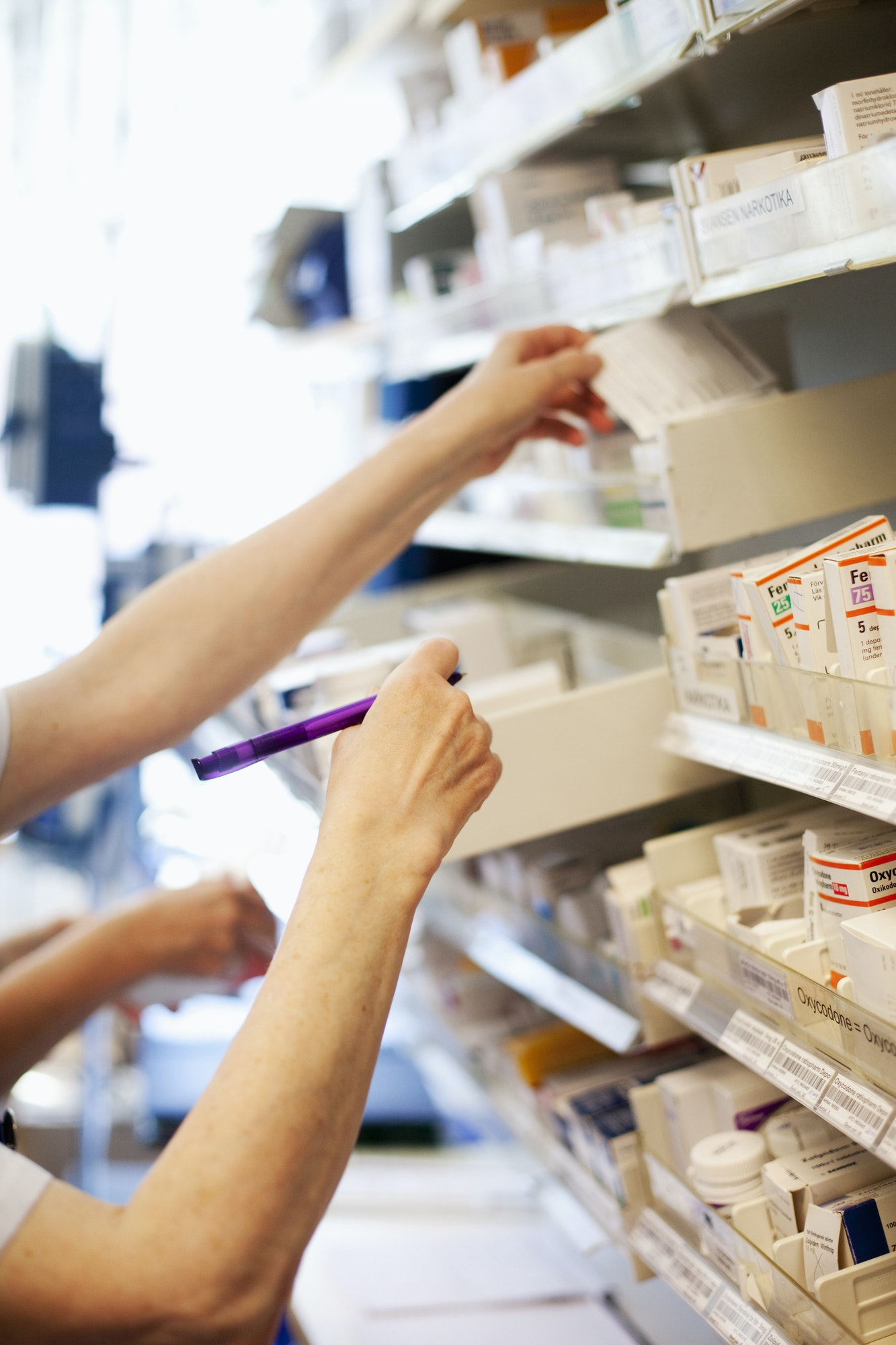 Cropped hands of woman picking medicine at pharmacy store