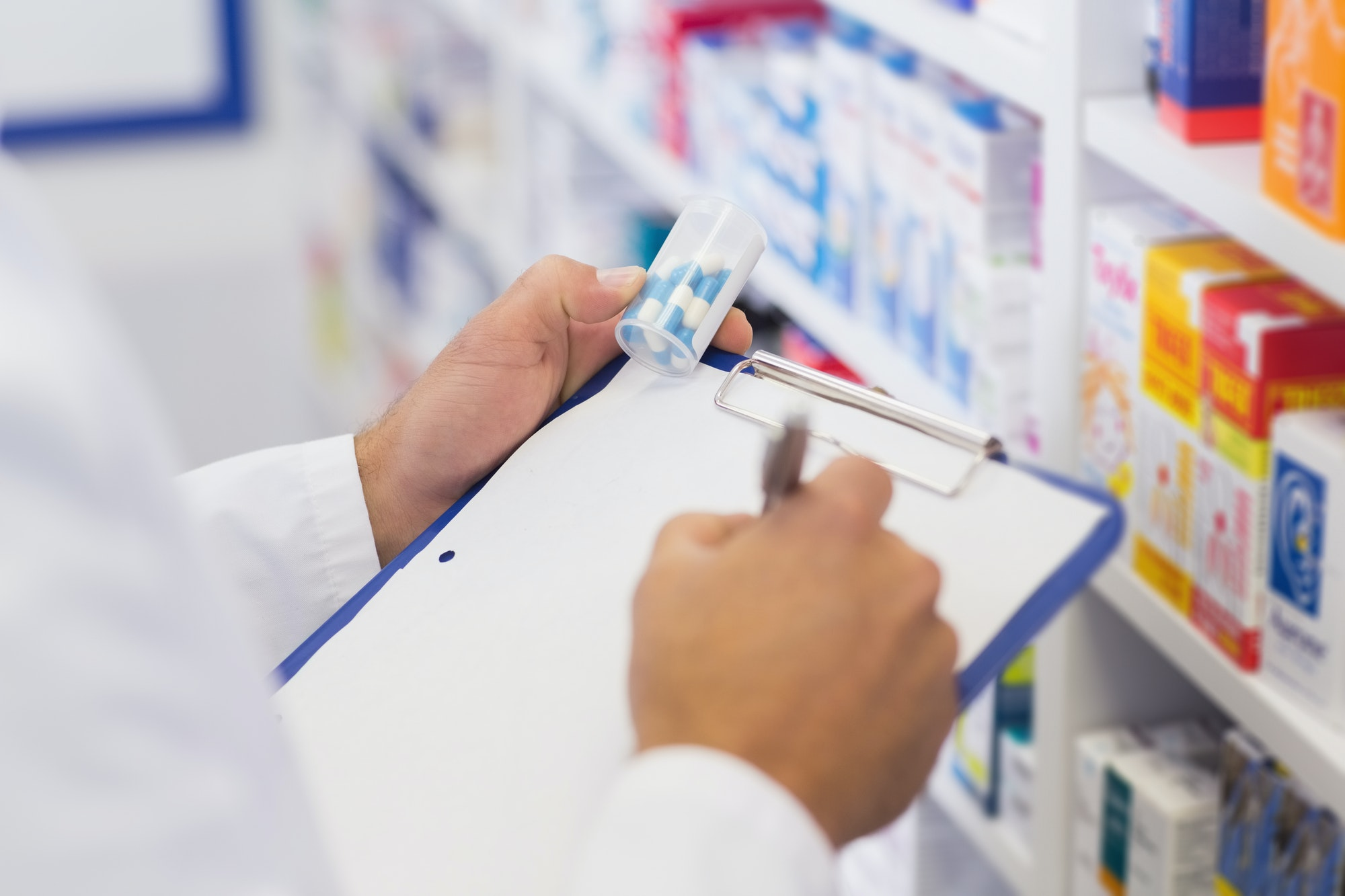 Pharmacist writing on clipboard and holding medicine jar at the hospital pharmacy