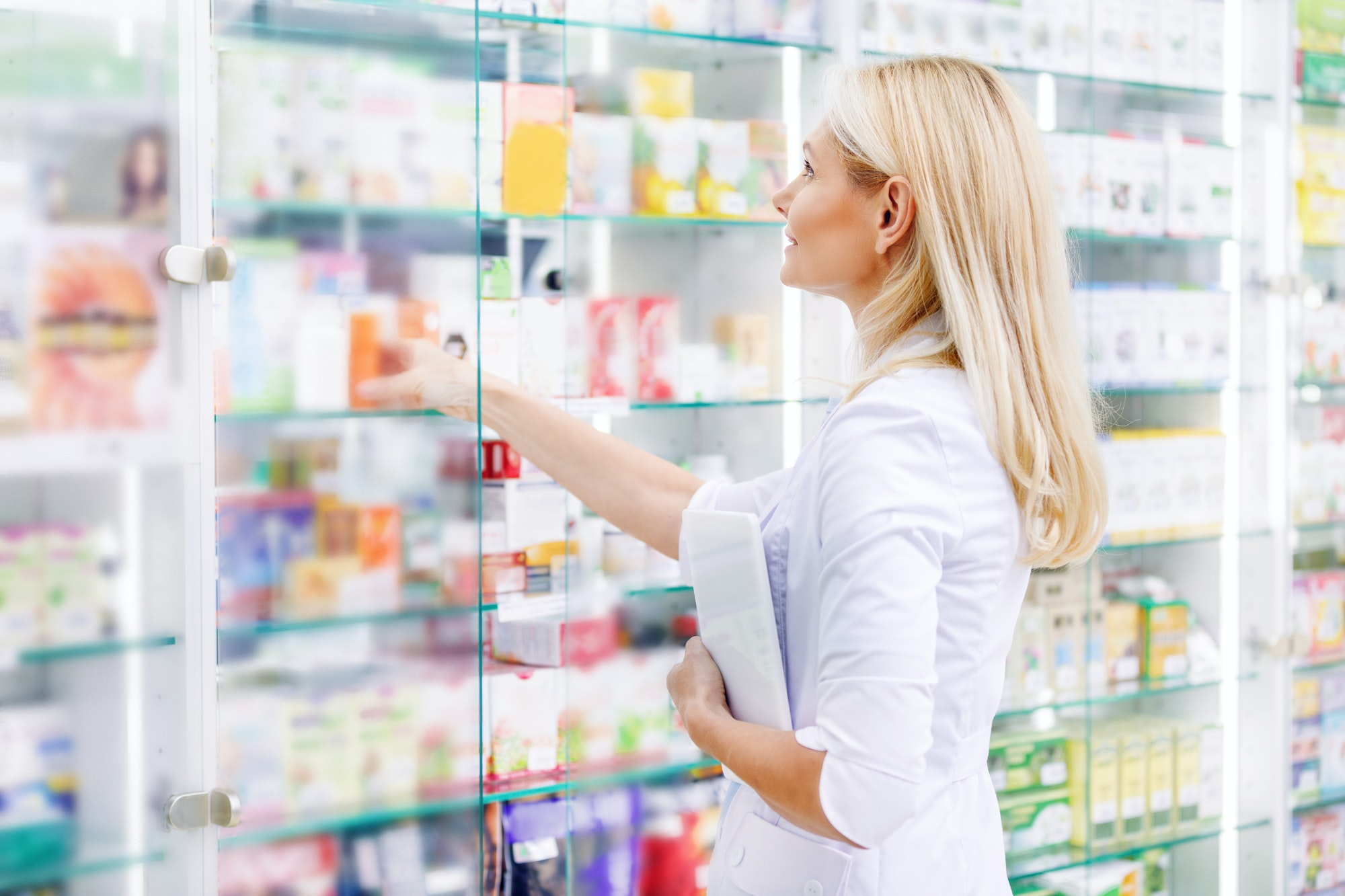 side view of pharmacist holding digital tablet and checking medications in drugstore