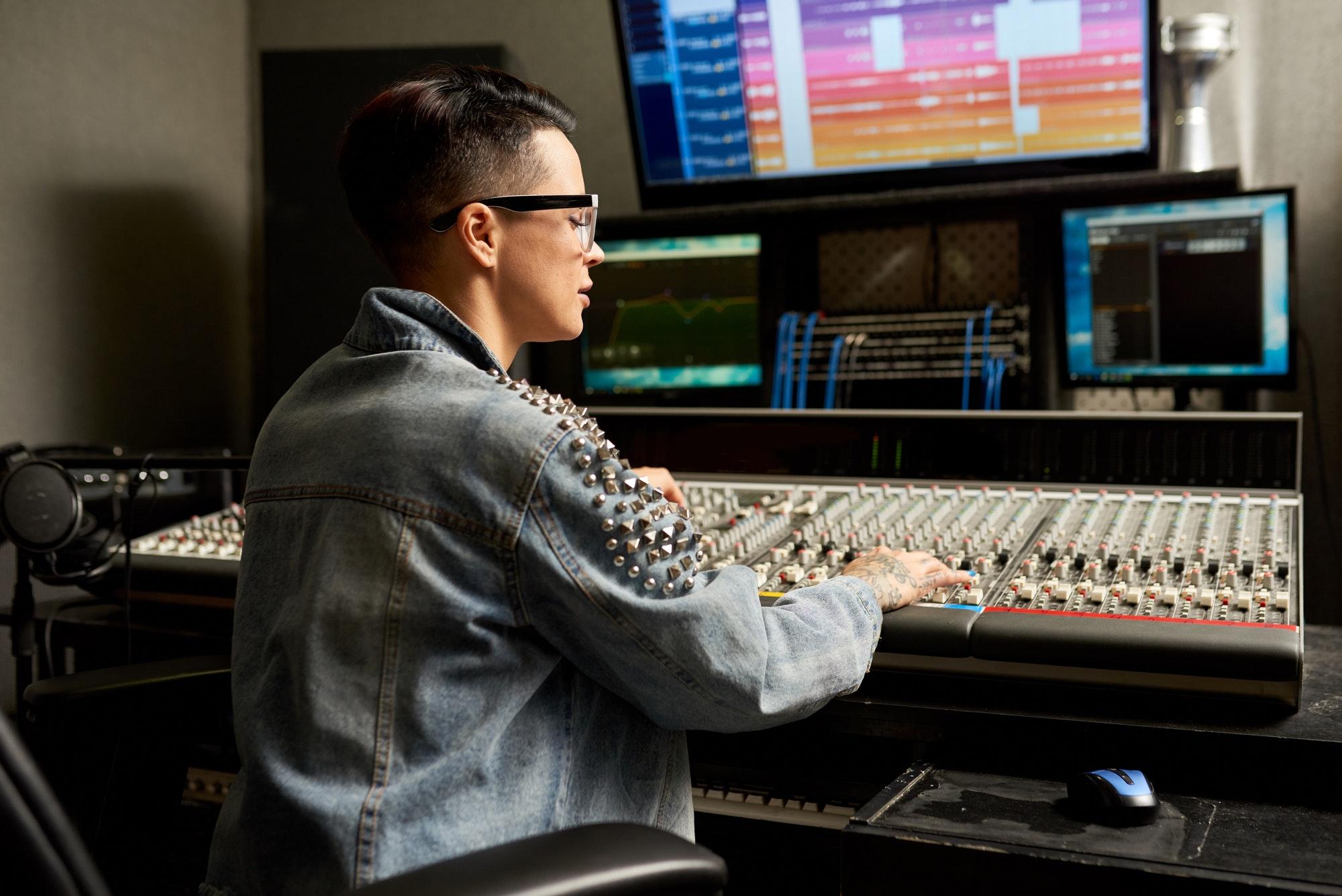 Concentrated audio engineer adjusting mixer in studio