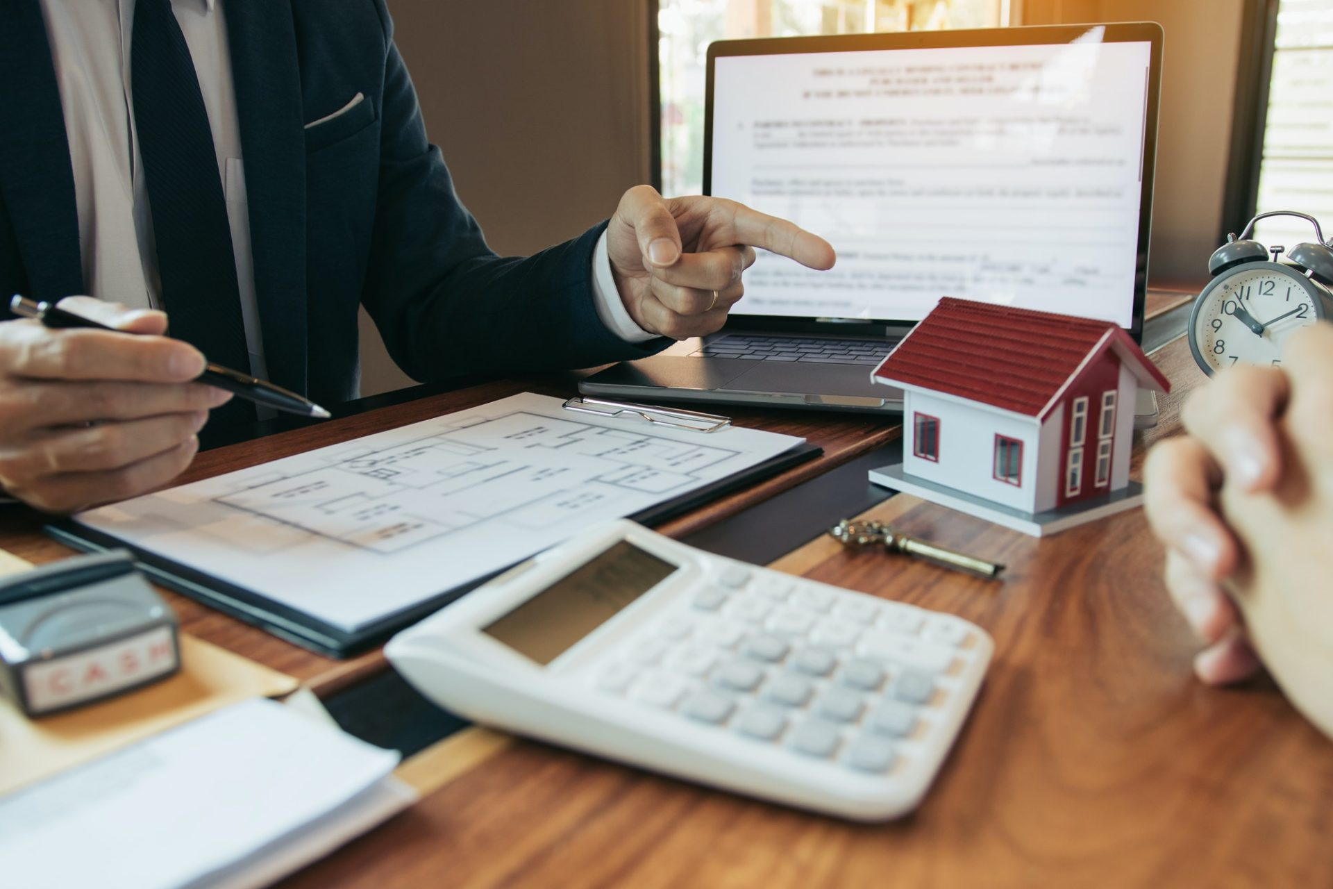 Property sales staff submit land mortgage contract documents to home buyers for sign.