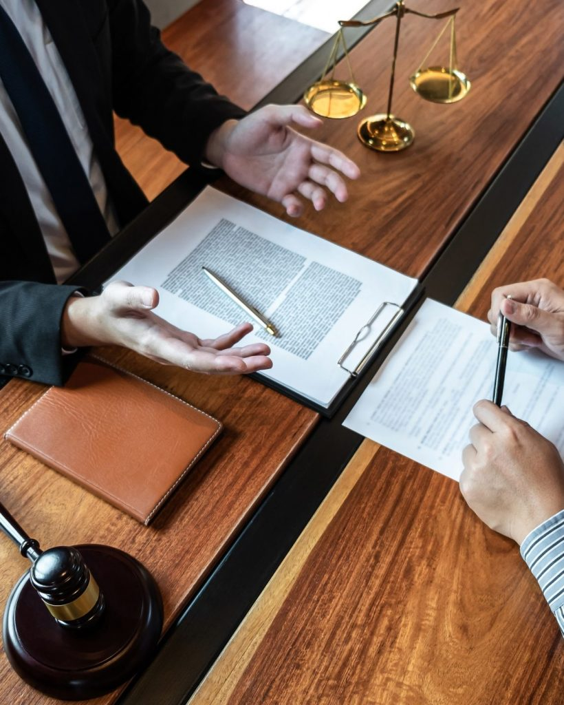 male lawyer discussing negotiation legal case with client meeting with document contract in office