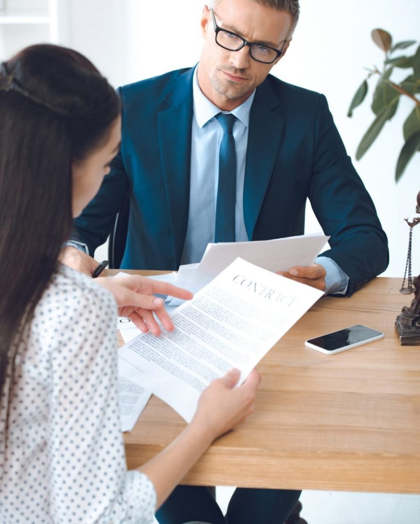 male lawyer looking at client reading contract