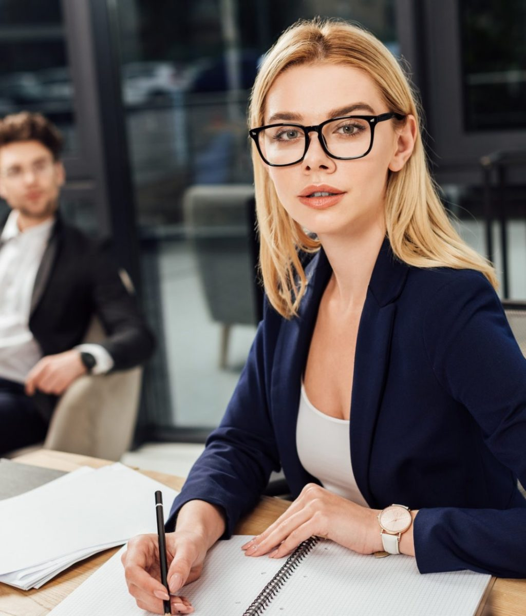 selective focus of businessman looking at businesswoman in eyeglasses that looking at camera at