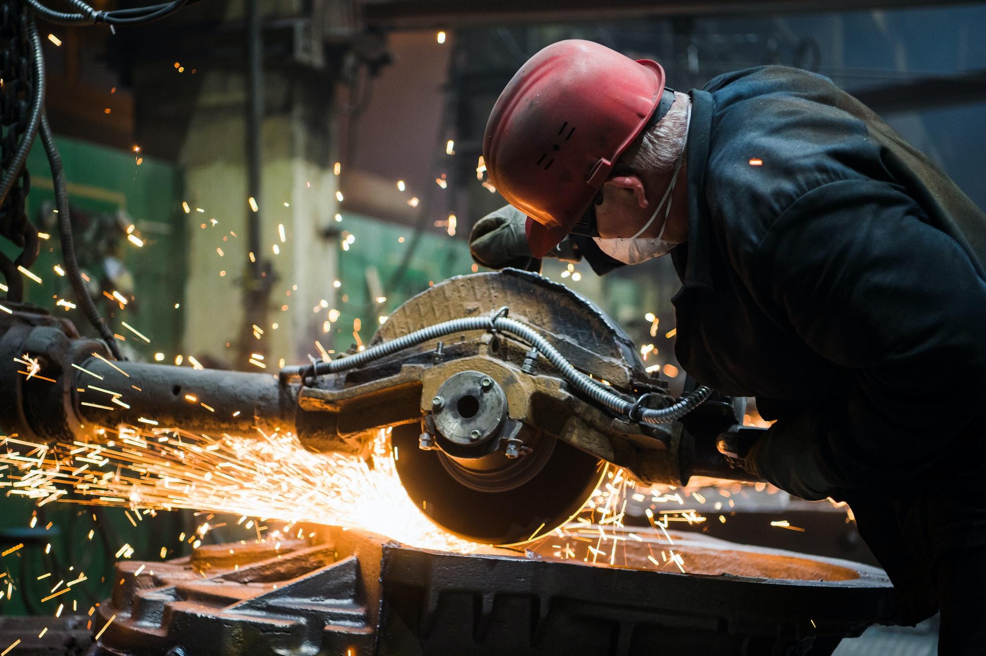 Worker grinding metal, metal grinding machine with sparks, metal sawing
