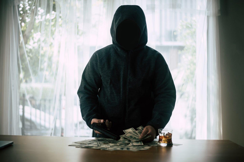 Hooded criminal gun shooting with dollar