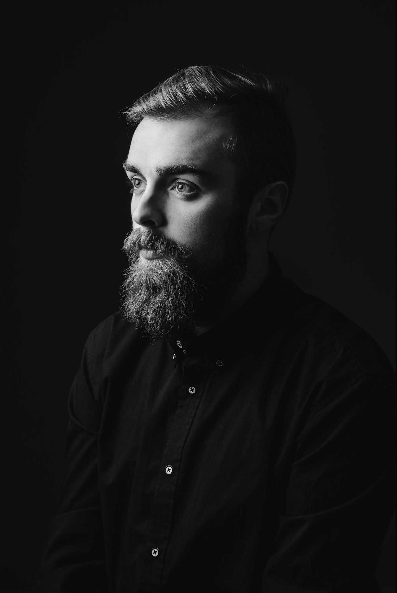 Black and white portrait of a stylish man with a beard and stylish hairdo dressed in the black shirt