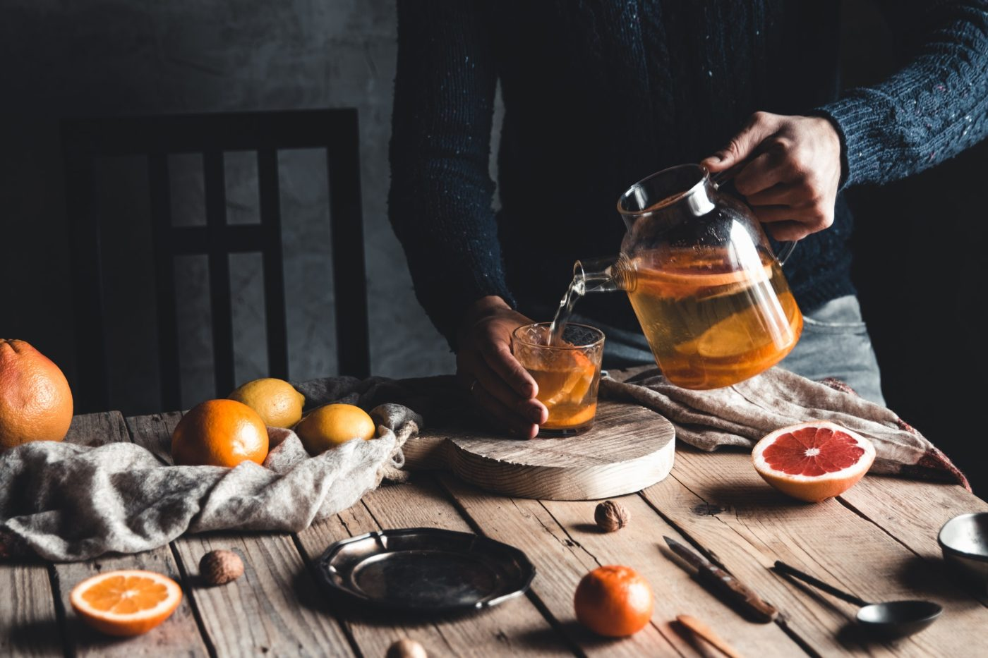 A man pours citrus tea on a wooden table. Healthy drink, vintage style. Vegan, eco products