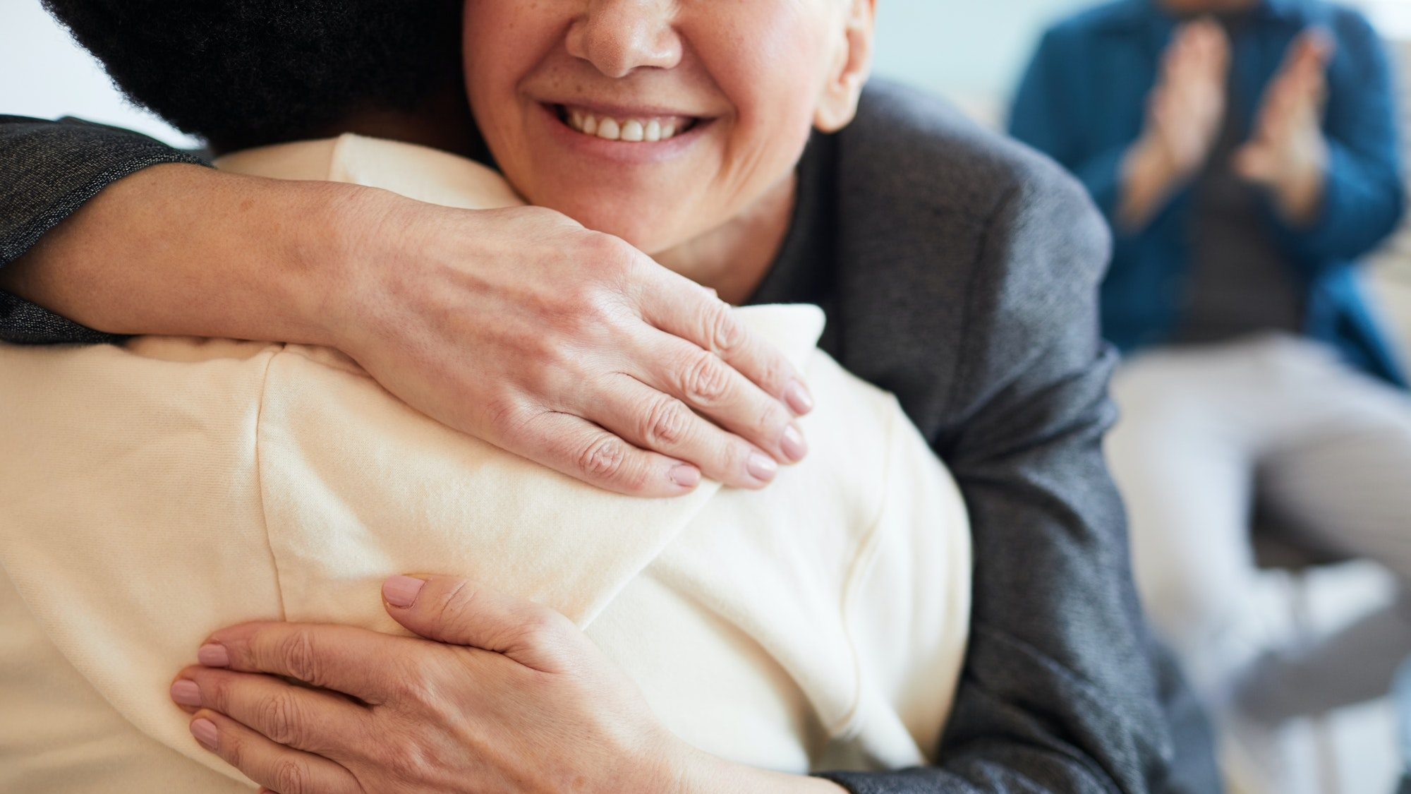 Smiling Psychologist Embracing Patient in Support Group