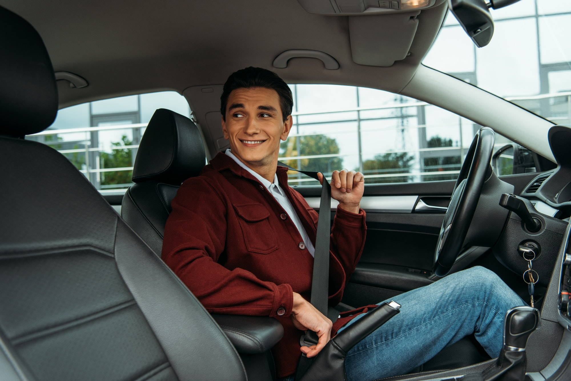 Smiling man holding safety belt in car and looking away