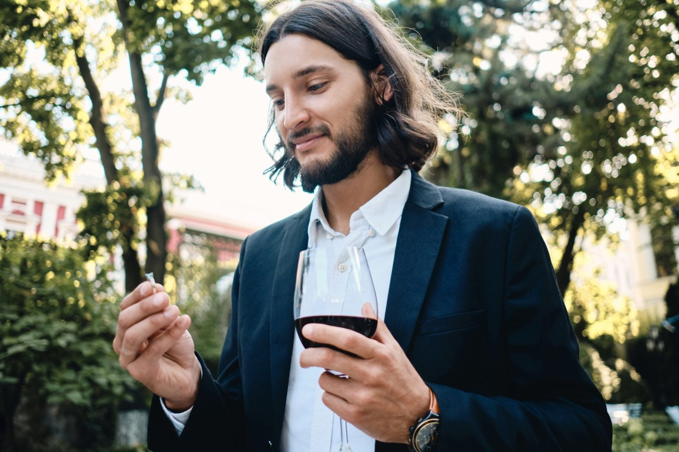 Young handsome latin man with glass of wine dreamily holding wedding ring in restaurant outdoor