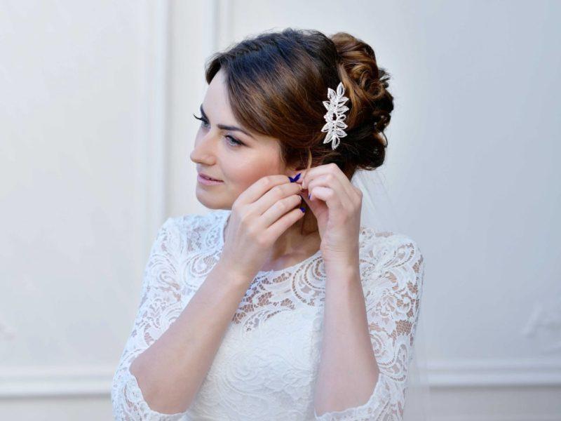beautiful-bride-in-white-wedding-dress-puts-on-ear-PZCF8HN
